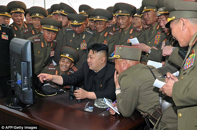 Kim Jong Un, pictured surrounded by military commanders, lashed out at Barack Obama, calling him a 'monkey' in a racist tirade following several internet outages