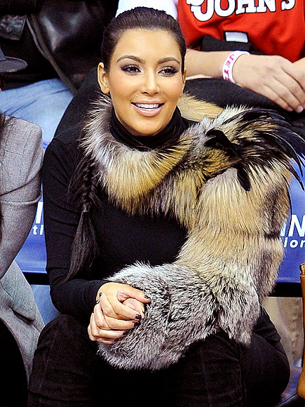 Kim Kardashian wears a one sleeved fur and feather crew nech shrug to a basketball game