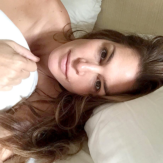 Cindy Crawford looks ageless in a makeup free face in bed as part of the #WakeUpCall campaign for Unicef